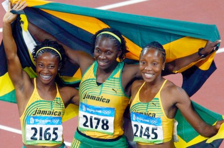 Fraser, Stewart and Simpson of Jamaica wave their national flag as they celebrate the victory of Fraser in the women's 100m final in the National Stadium at the Beijing 2008 Olympic Games